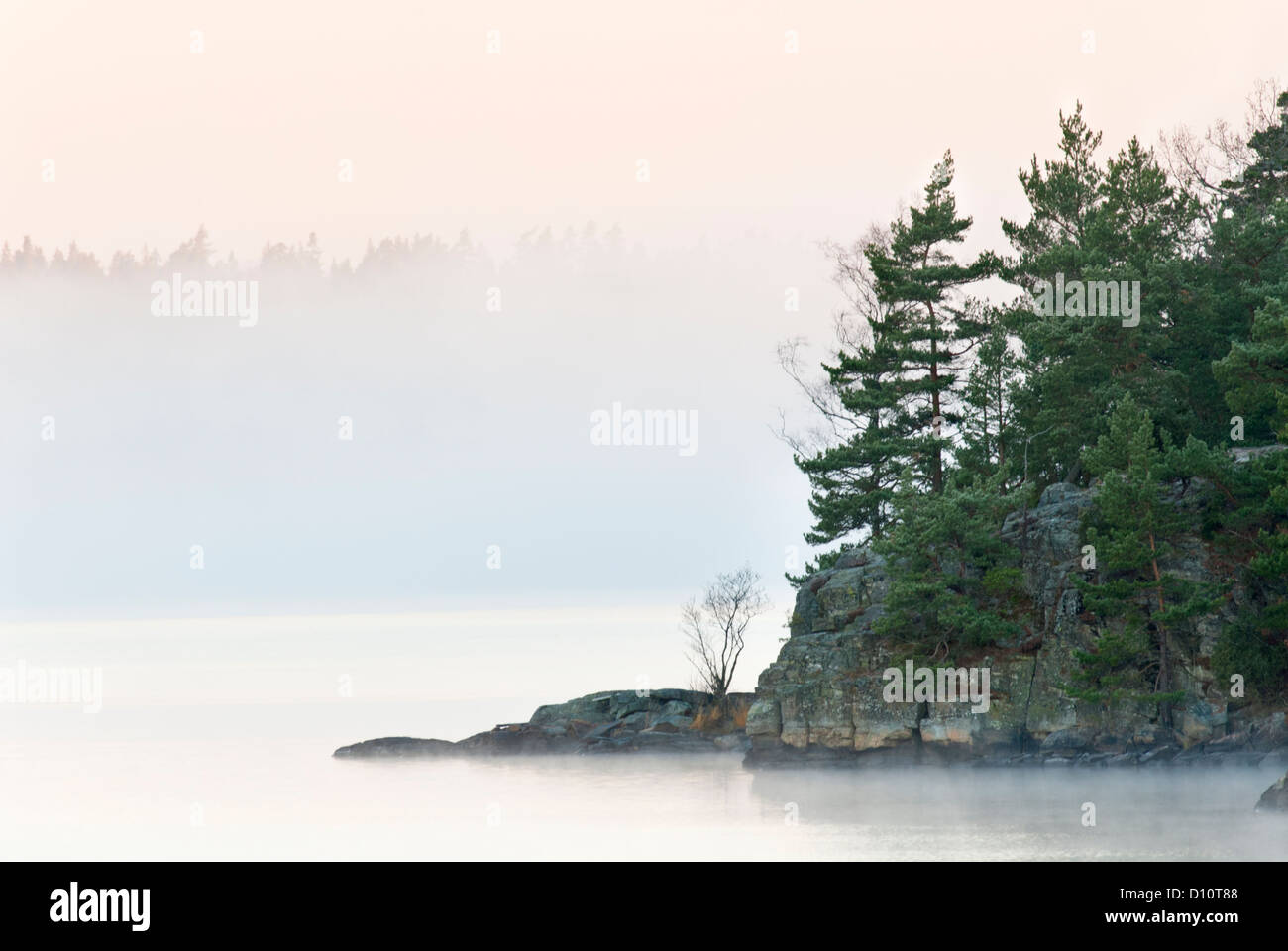 Cape in a calm lake and early morning mist. - Stock Image