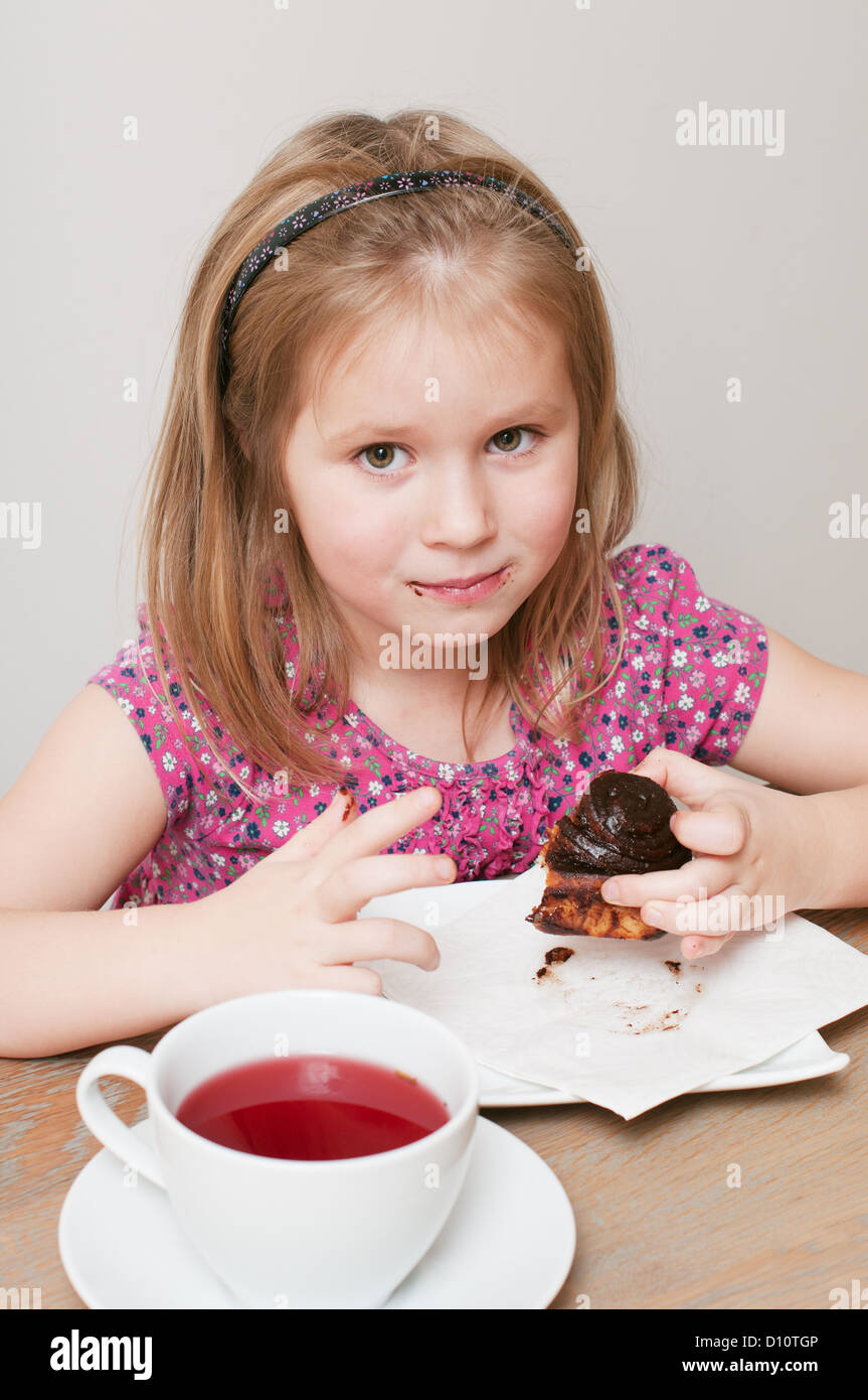 Indoor photo of a little girl with cup of fruit tea eating piece of chocolate pie - Stock Image