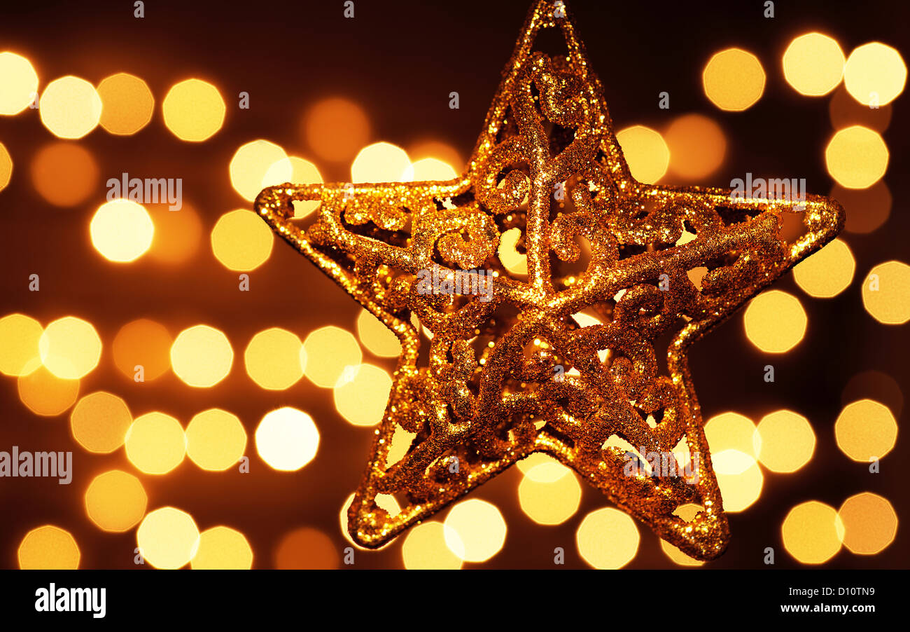 image of beautiful golden star decoration isolated on festive blur lights background christmas eve
