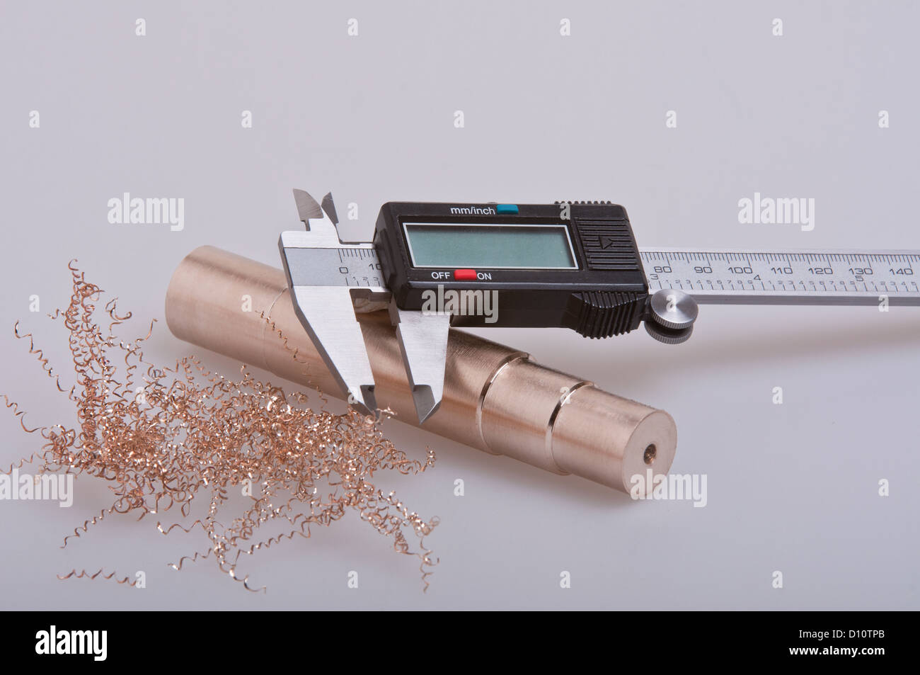 A pair of digital calipers / veriners used for measuring,  resting on a spigot of  bronze with some bronze swarf - Stock Image