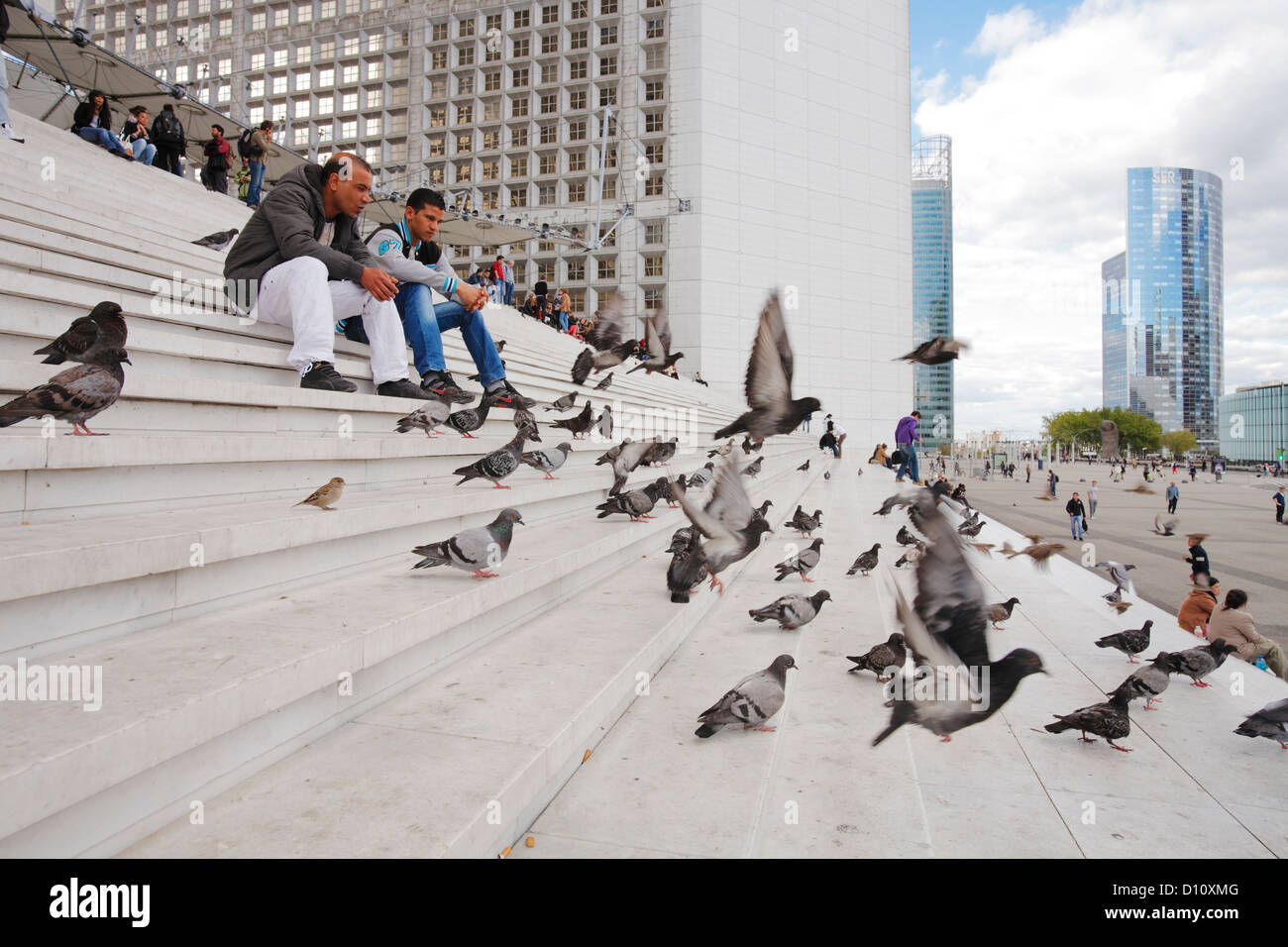 two men talking on stairs of La Grande Arche in Paris - Stock Image