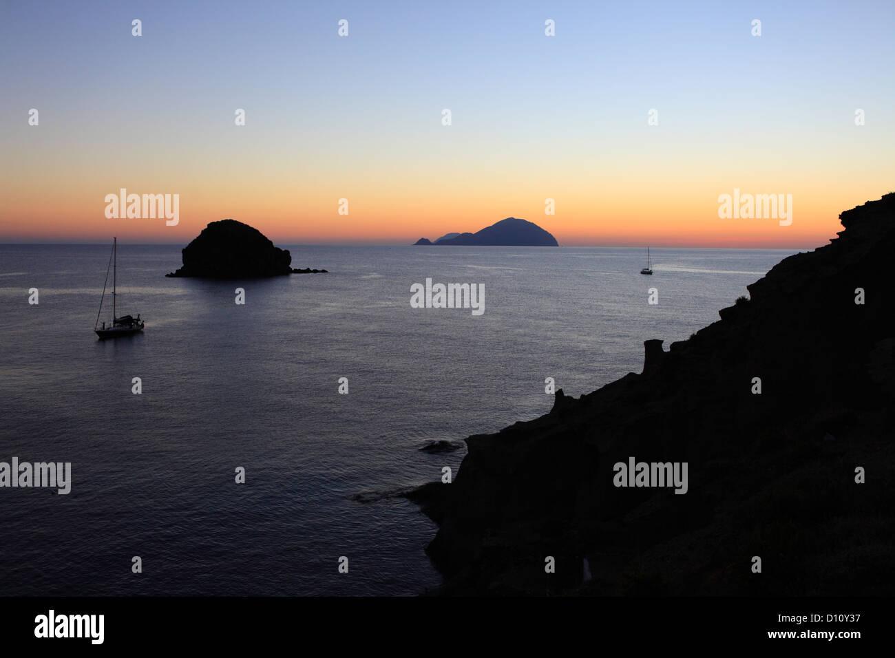 Faraglione rocks and Filicudi island seen from Pollara, Salina, Aeolian islands, Sicily, Italy Stock Photo