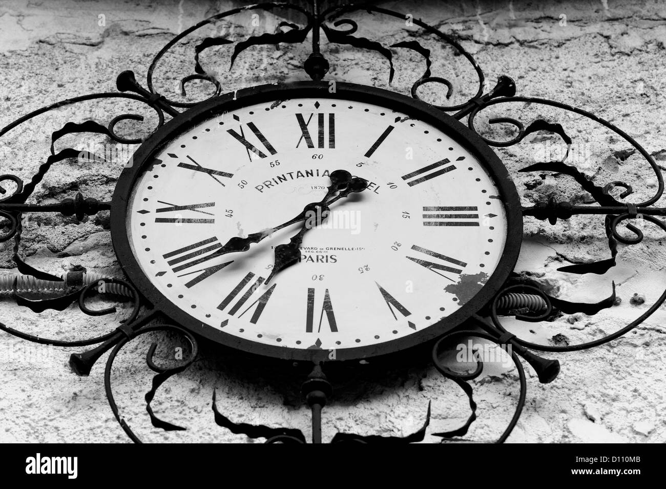 Old clock hanging against a wall in a Tuscan Village in Italy - Stock Image