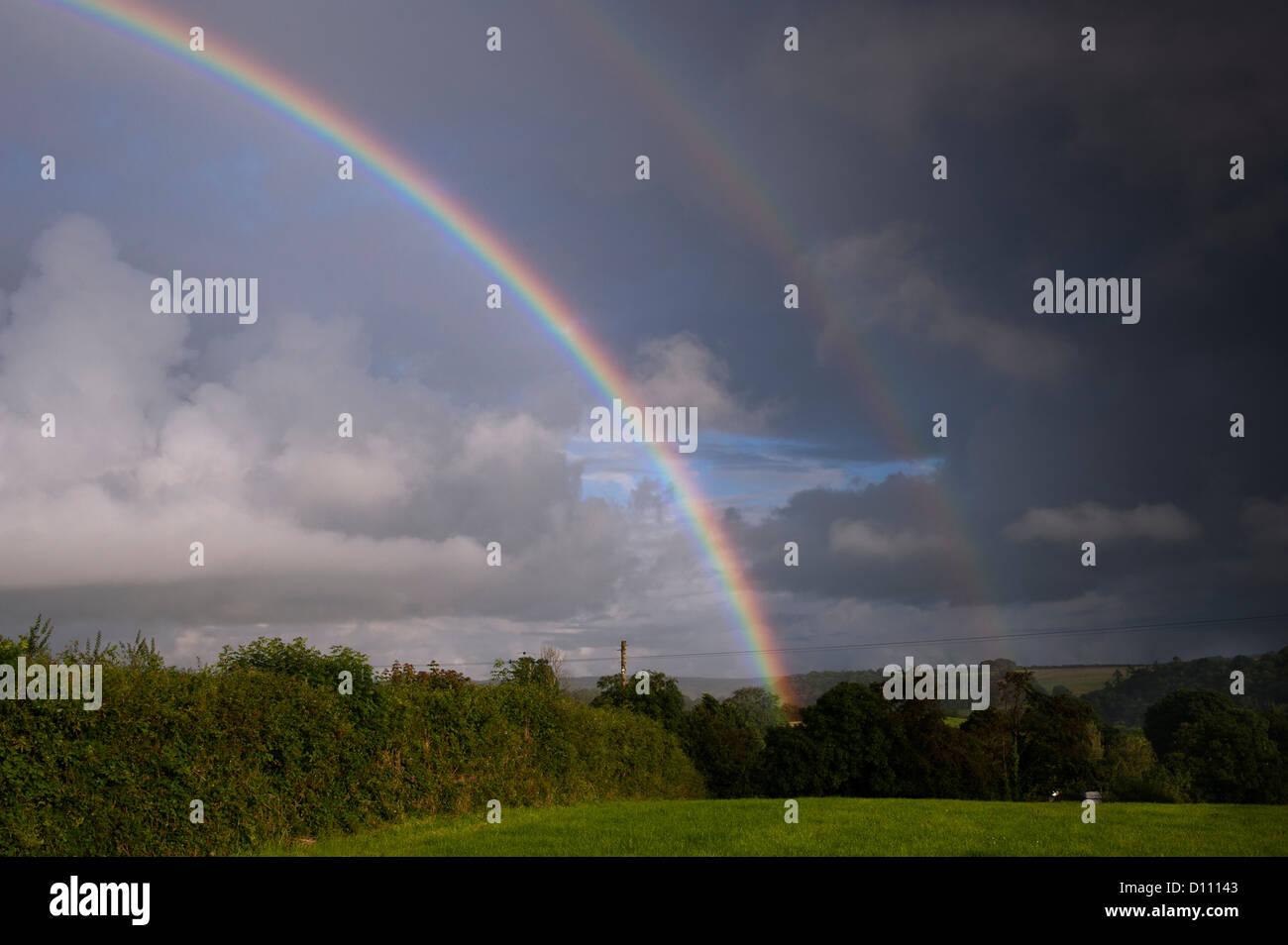 Double rainbow over farmland in North Cornwall, UK. Stock Photo