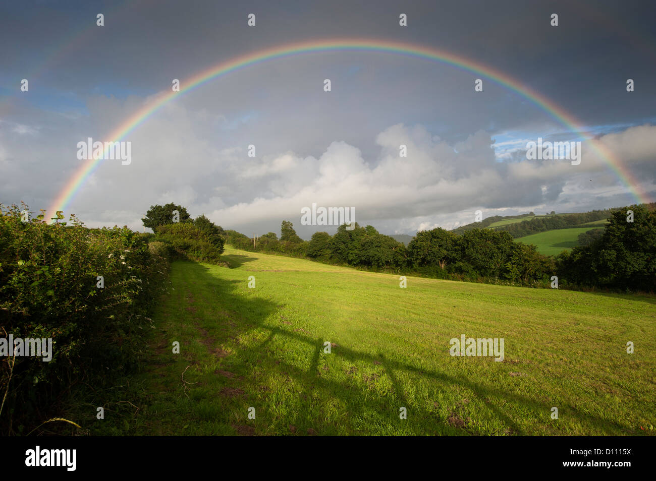 Rainbow over farmland in North Cornwall, UK - Stock Image