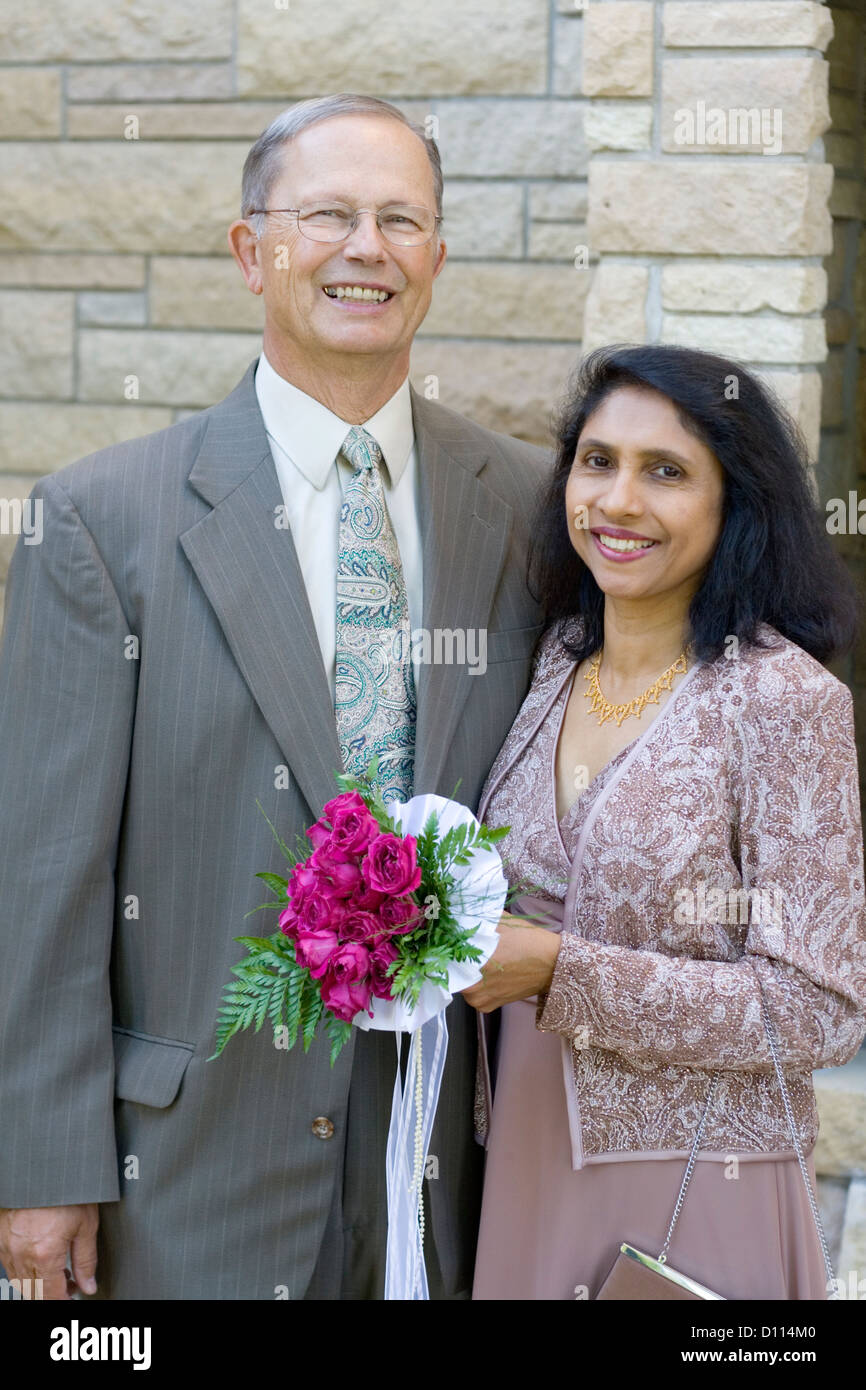 East Indian American bride and white husband age 59 and 67 after marriage in Catholic Church. Minneapolis Minnesota - Stock Image