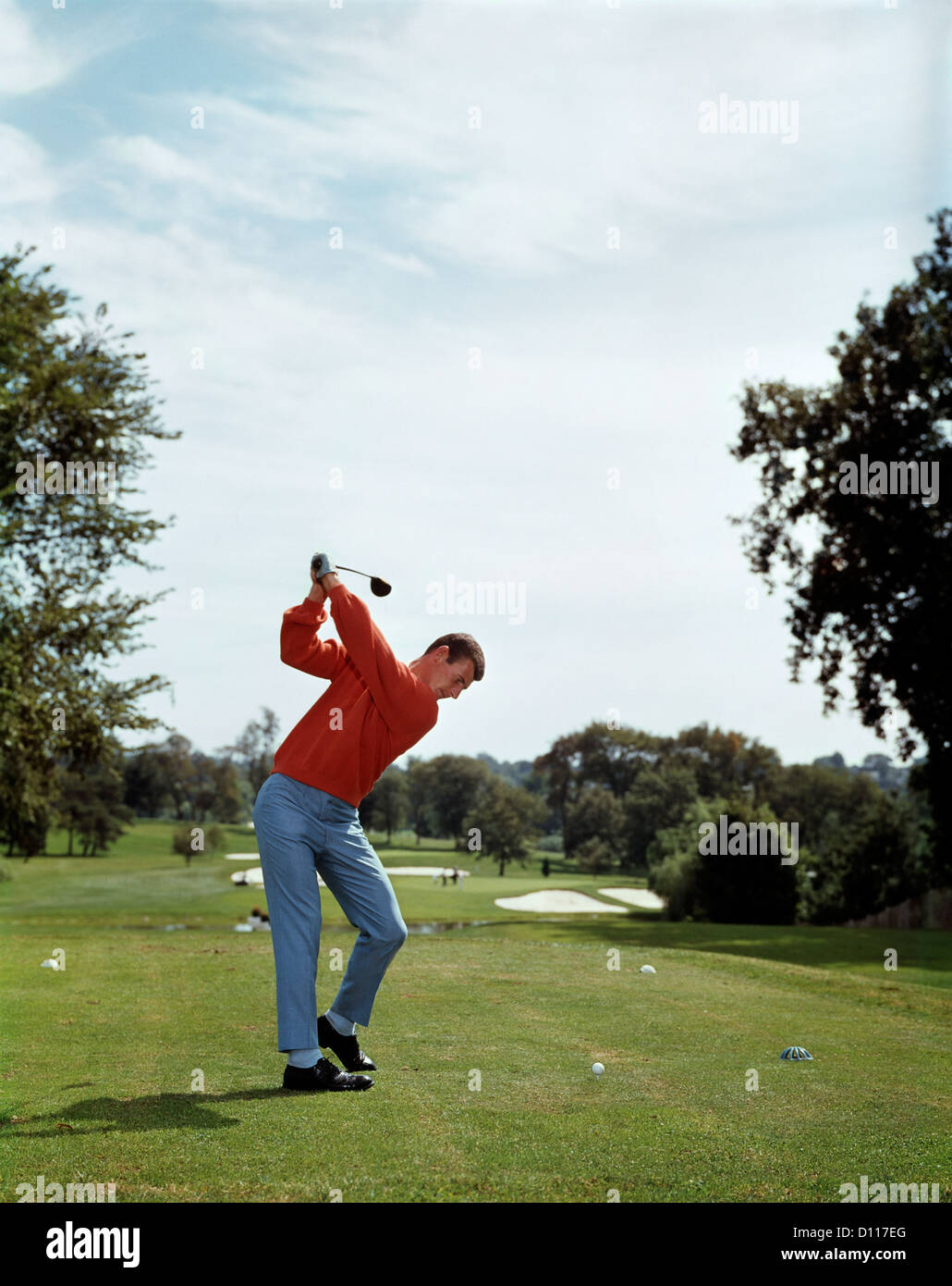 GOLFER TEEING OFF DOWN FAIRWAY ON GOLF COURSE - Stock Image