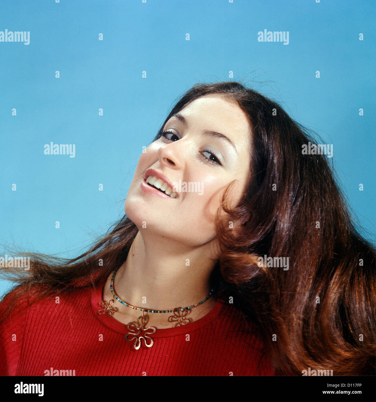1960s 1970s PORTRAIT OF SMILING WOMAN TOSSING BACK HER LONG BROWN HAIR WEARING RED TOP LOOKING AT CAMERA Stock Photo