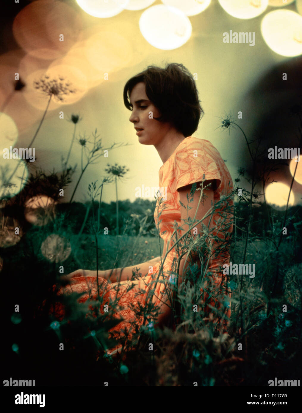 1970s SERIOUS WOMAN IN FIELD FLOWERS WITH SOFT FOCUS SPECIAL EFFECT - Stock Image