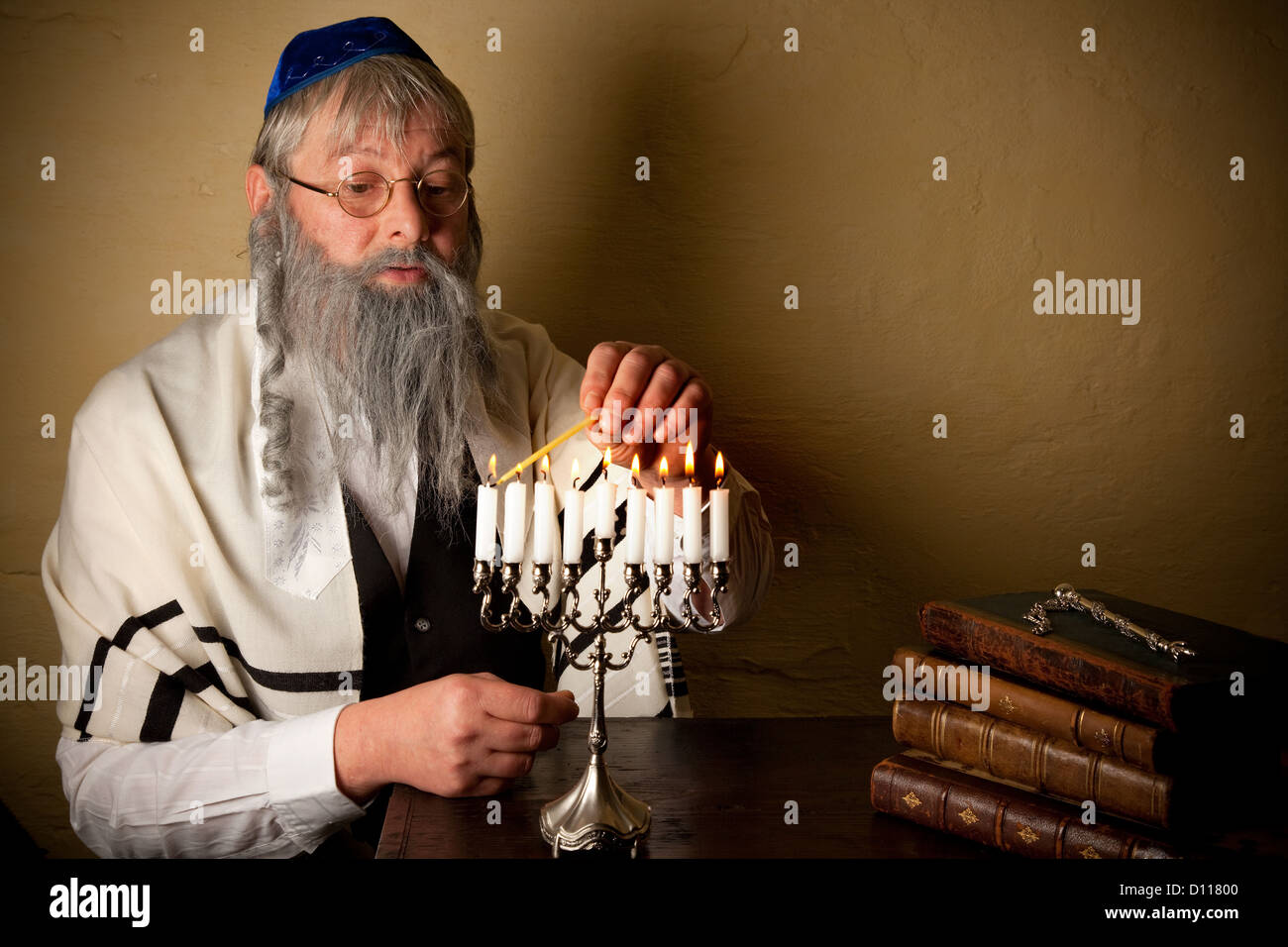 Old jewish man with beard lighting candles for hannukah - Stock Image