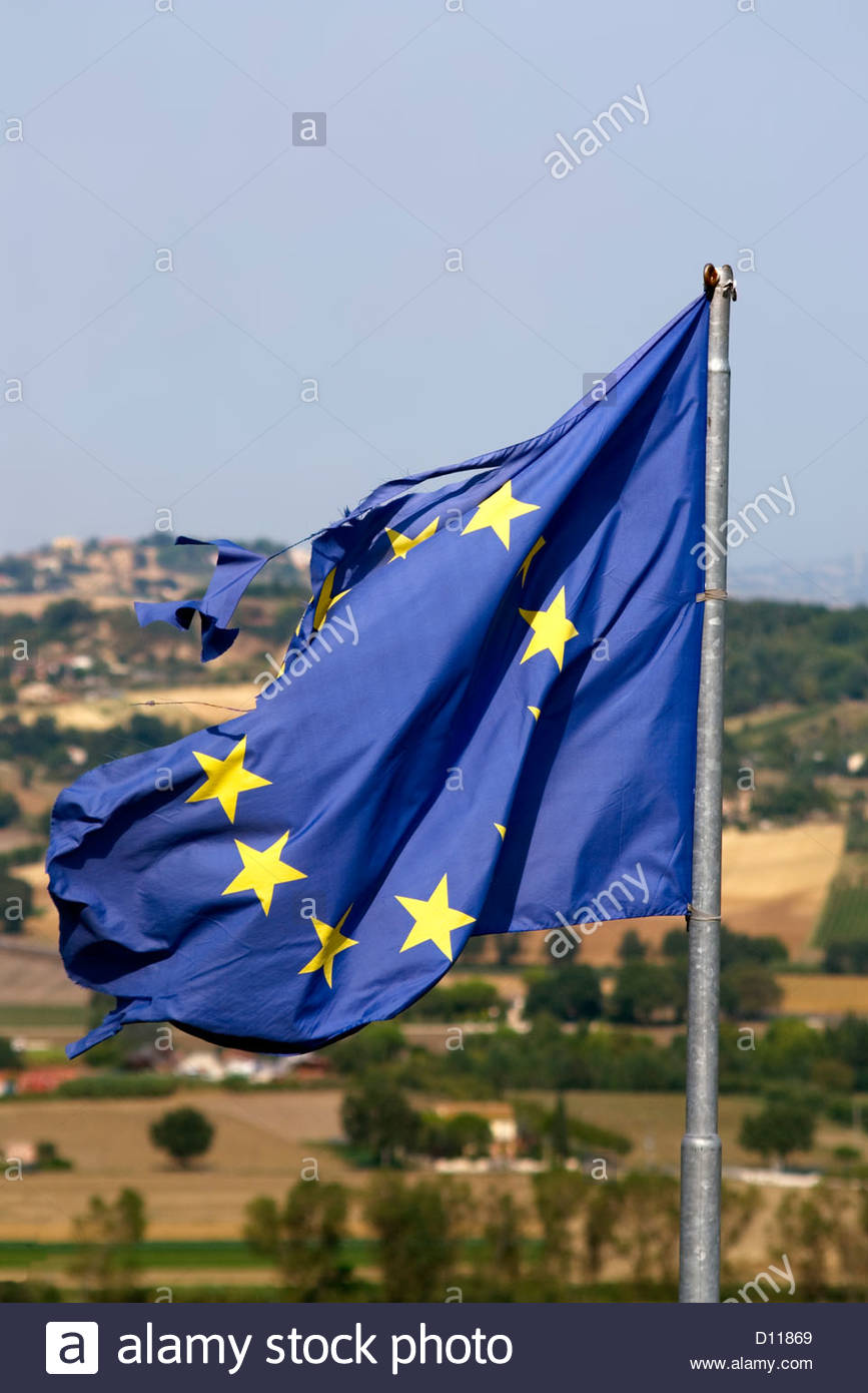 Wind torn European Union Flag on a flag pole | Vom Wind zerissene Flagge der Europaeischen Union am Flaggenmast - Stock Image