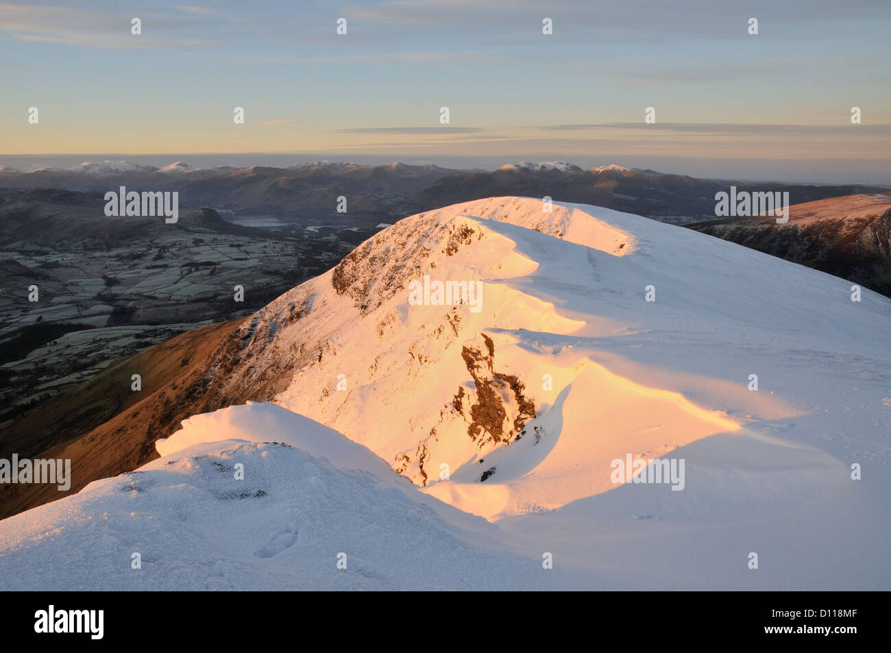 Dawn sunlight on the snow clad summit ridge of Blencathra in the English Lake District - Stock Image