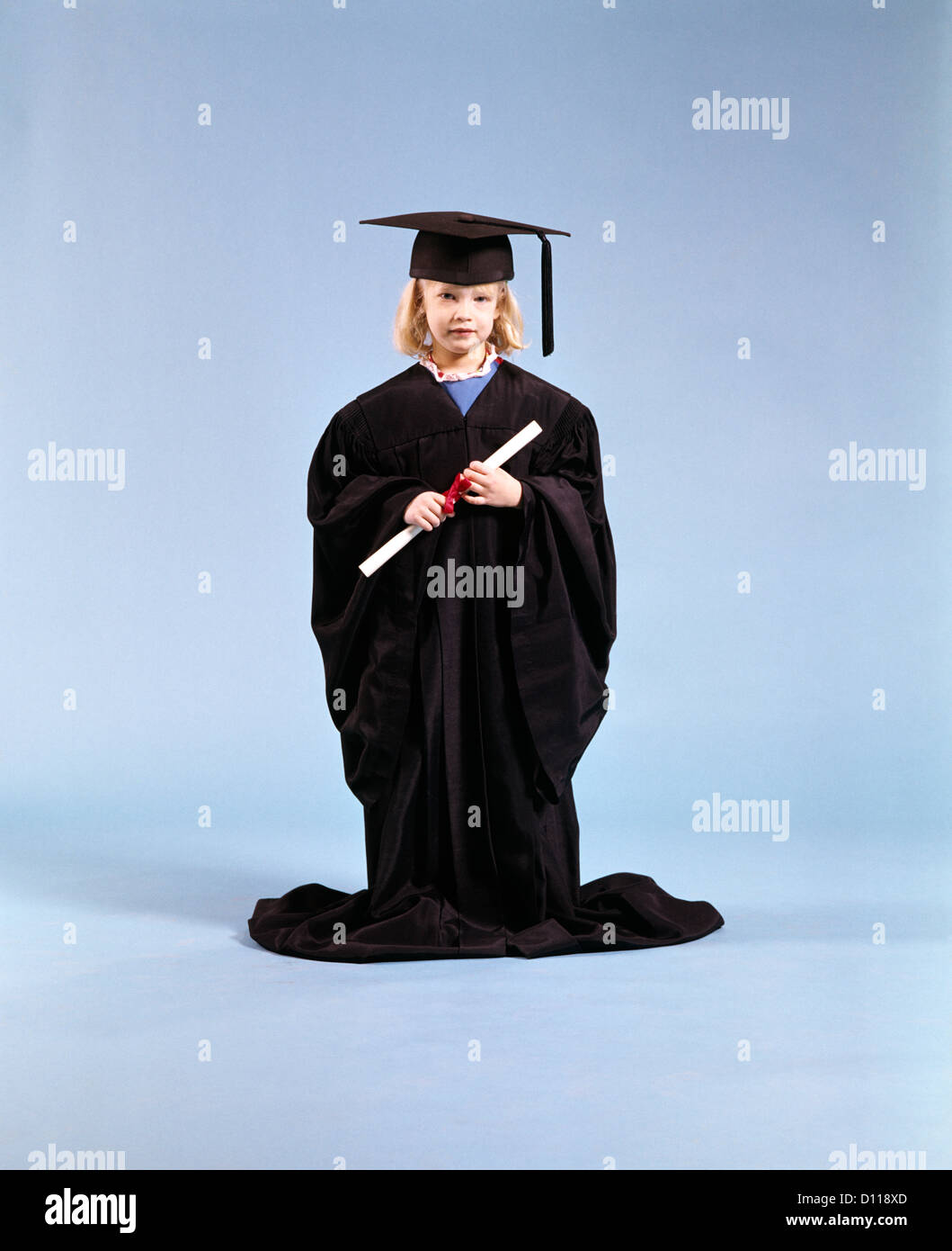 1980s LITTLE GIRL WEARING TOO BIG GRADUATION CAP AND GOWN HOLDING ...