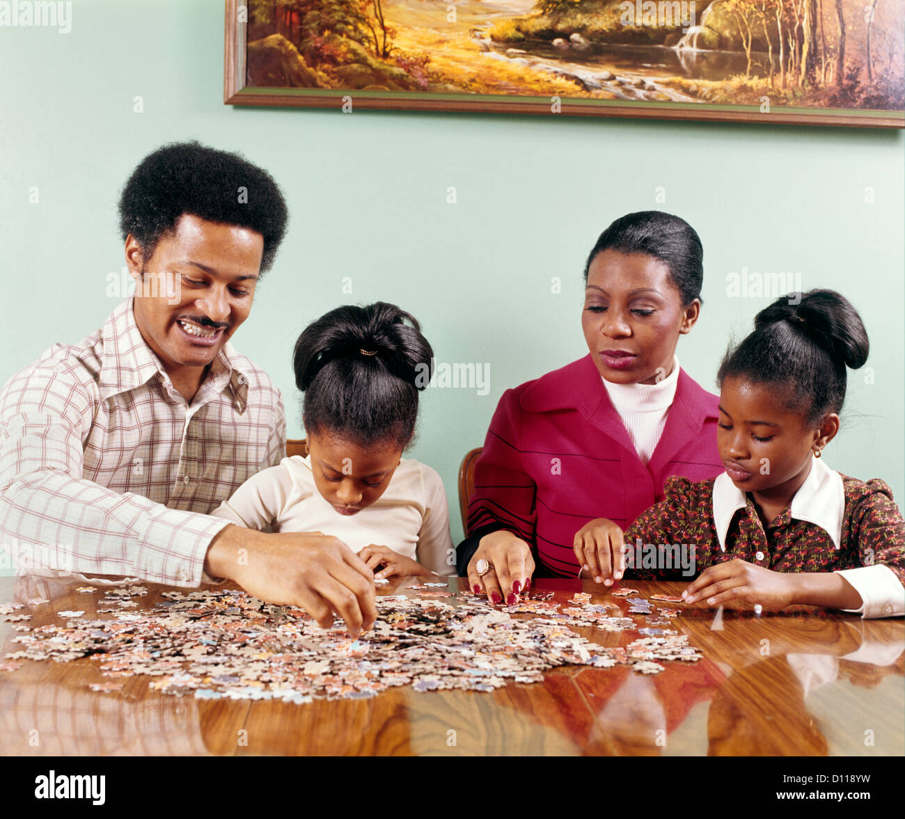 1970s AFRICAN-AMERICAN FAMILY MAN WOMAN MOTHER FATHER TWO CHILDREN GIRLS SITTING TABLE DOING JIGSAW PUZZLE RETRO - Stock Image