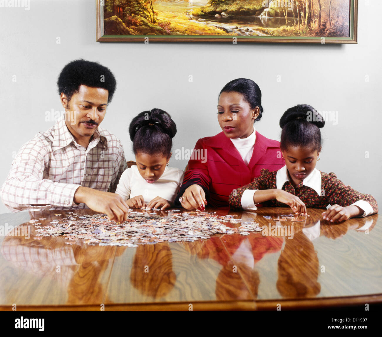 1970s AFRICAN AMERICAN FAMILY FATHER MOTHER TWO DAUGHTERS SITTING AT TABLE DOING JIGSAW PUZZLE - Stock Image