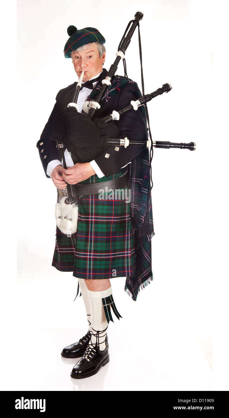 Scottish highlander wearing kilt and playing bagpipes - Stock Image
