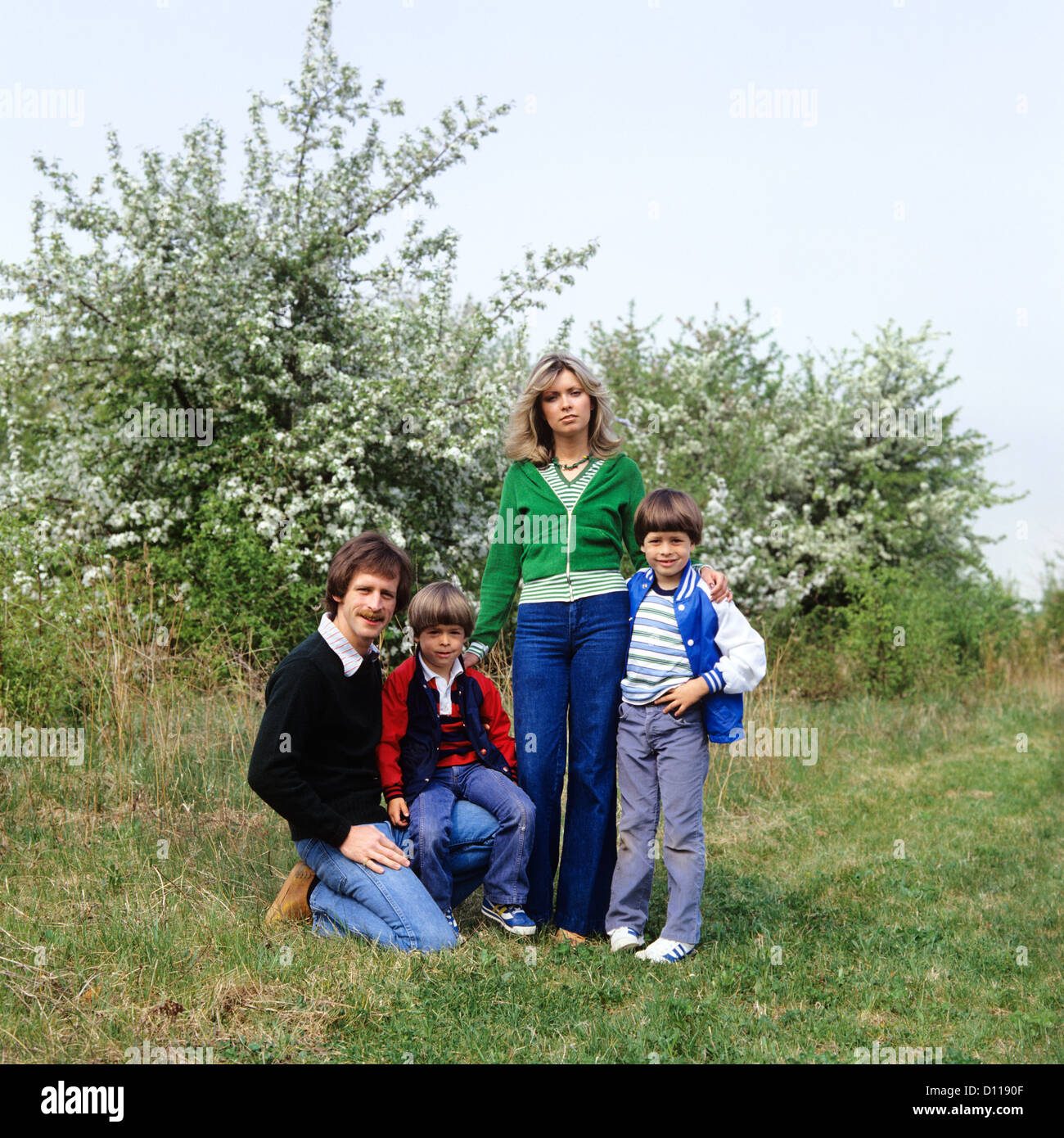 1970s PORTRAIT FAMILY STANDING IN ORCHARD MOTHER FATHER TWO BOYS - Stock Image