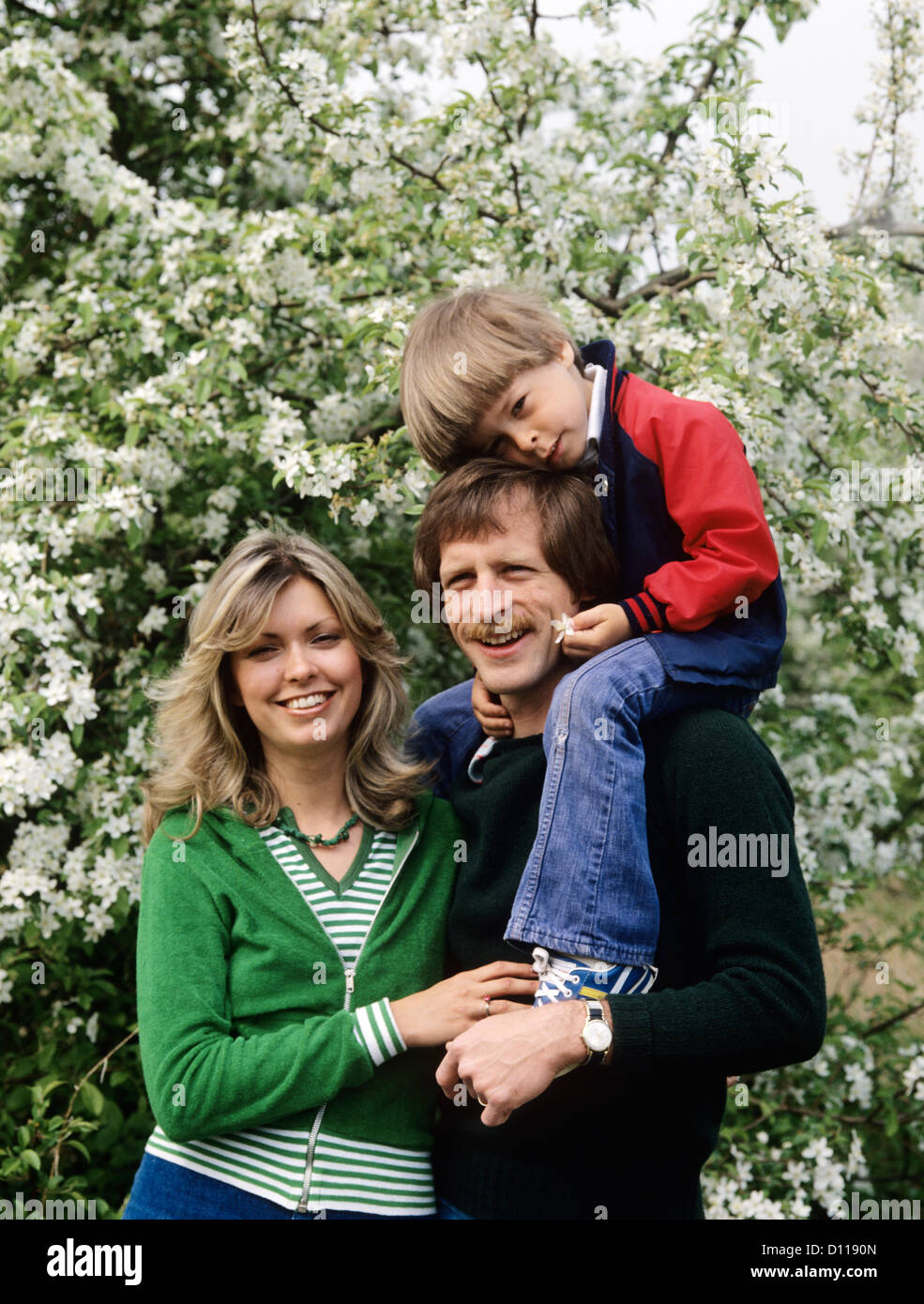 1970s FAMILY OUTDOORS MOTHER AND FATHER CARRYING SON ON SHOULDERS - Stock Image