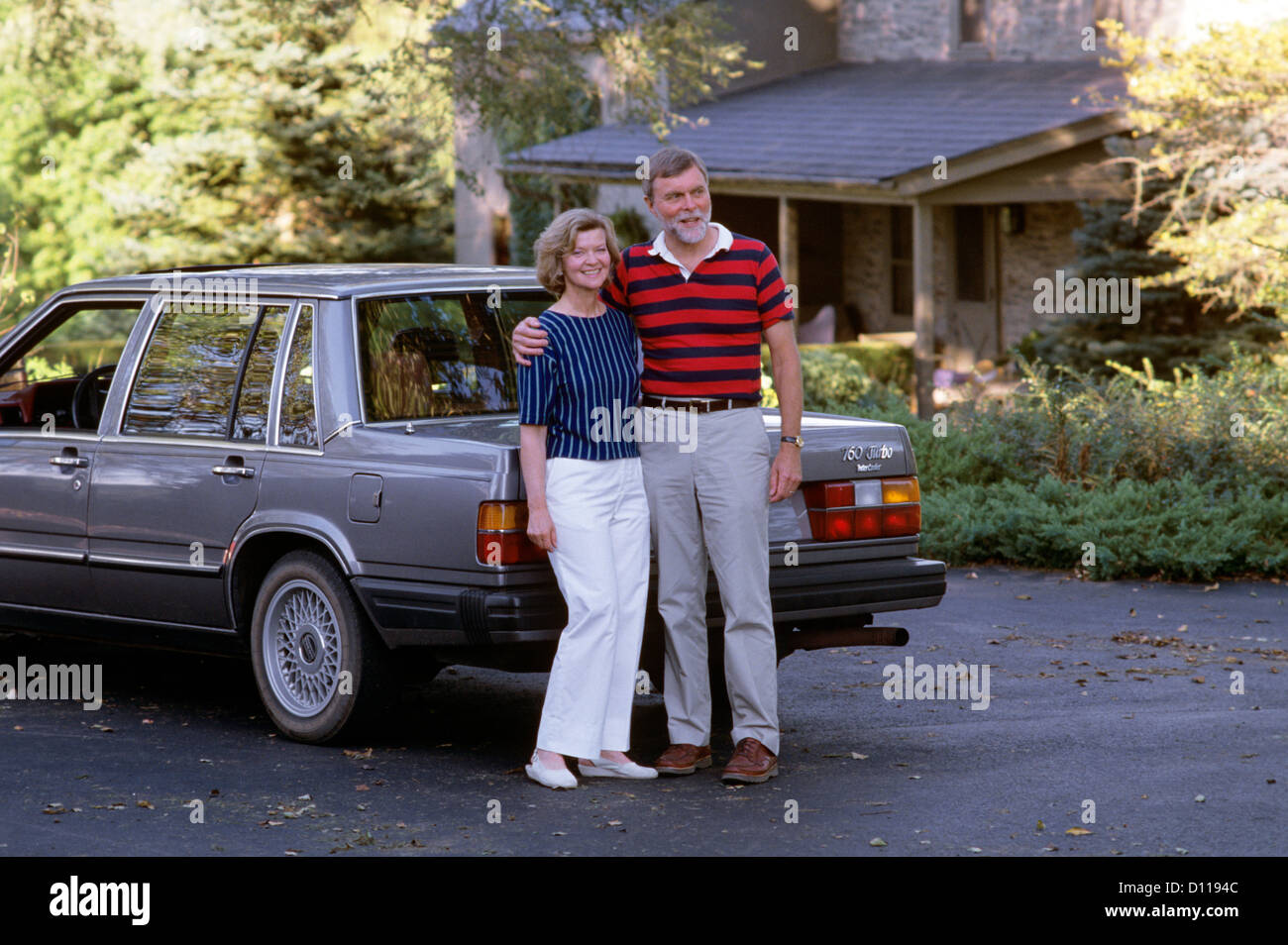 1980s SMILING COUPLE IN DRIVEWAY WITH CAR - Stock Image