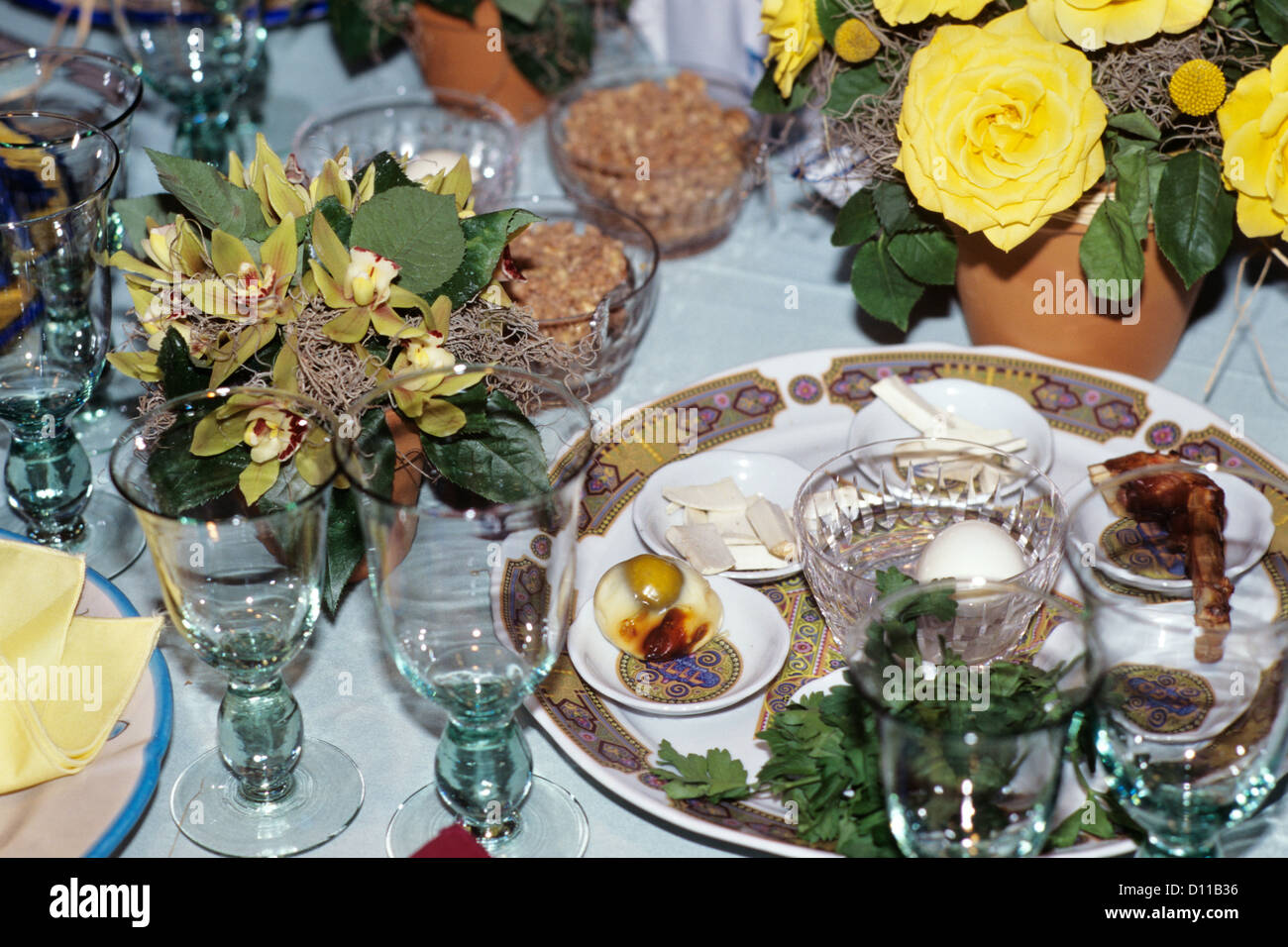 1990s PLACE SETTING FOR PASSOVER SEDER ON TABLE WITH FLORAL CENTERPIECE - Stock Image