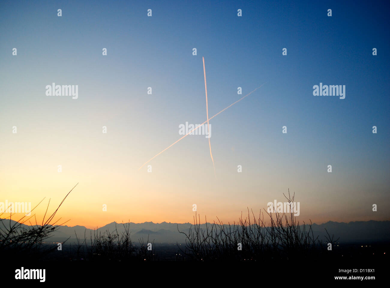 Aircraft trails crossing each others on Turin skyes at the dusk with Alps background. - Stock Image