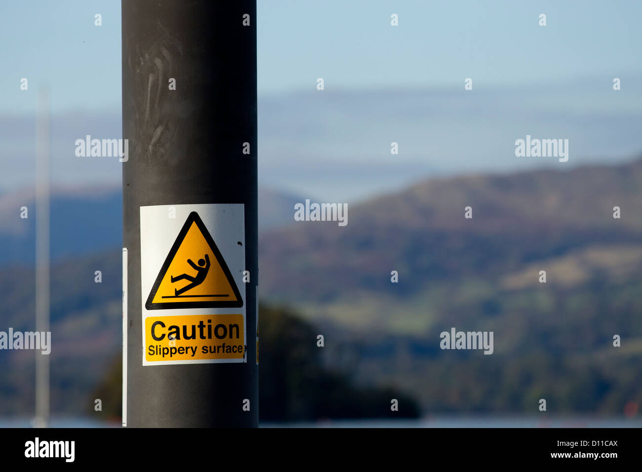 caution slippery surface sign on jetty  on Lake Windermere - Stock Image
