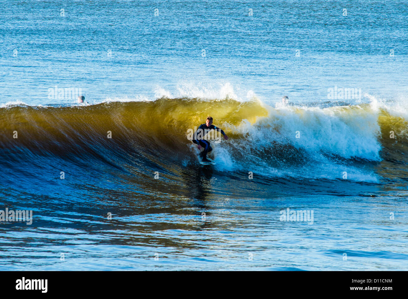 Aberystwyth Wales UK Surfers riding the waves at the mouth of the harbour in the warm autumn sunshine - Stock Image