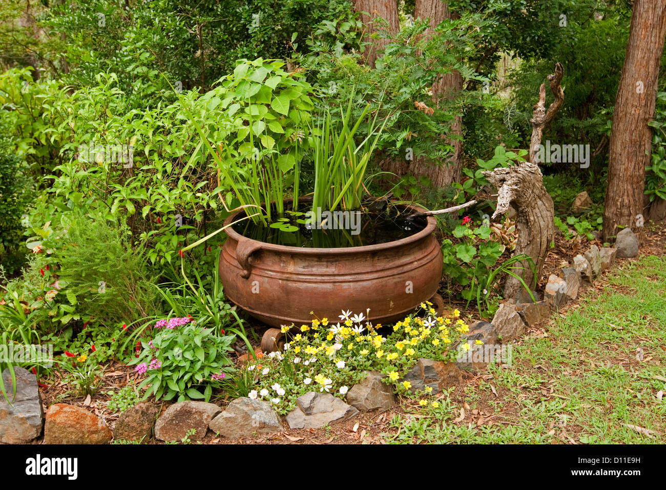 Ornate garden pond - large rusty cauldron as a water feature with aquatic plants and surrounded by colorful flowering - Stock Image