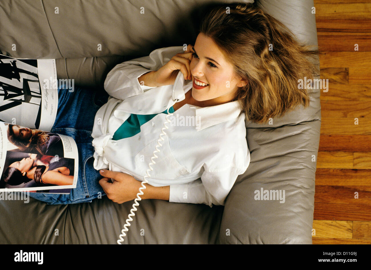 1990s WOMAN WHITE BLOUSE SOFA COUCH TALKING TELEPHONE - Stock Image