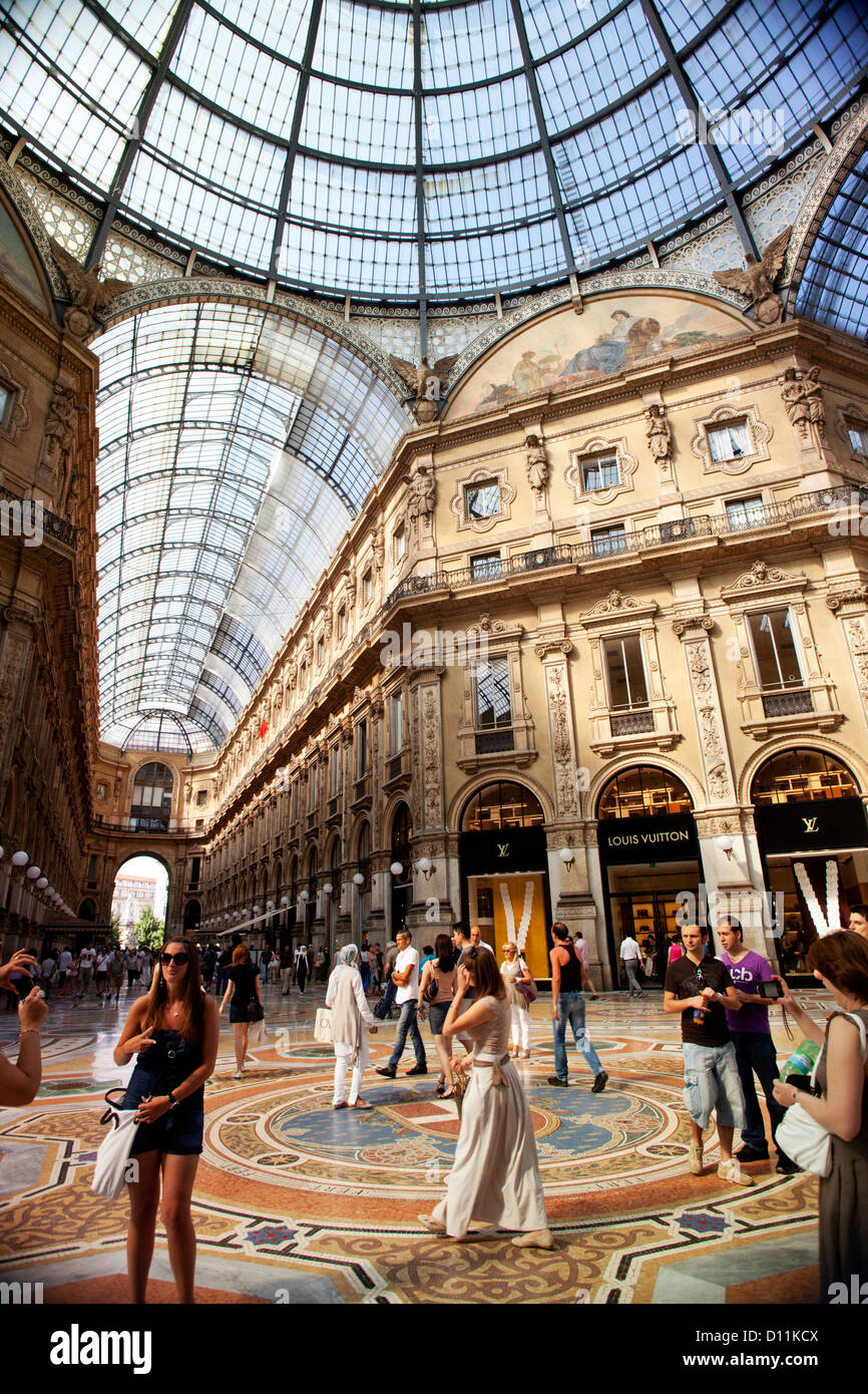 Tourists visiting the Galleria Vittorio Emanuele with its prestigious stores in Milan, Italy - Stock Image