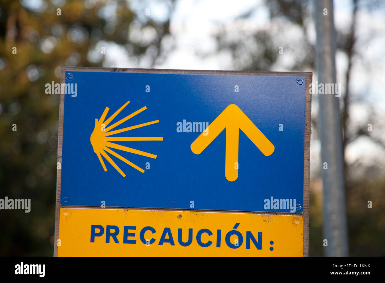 Camino precaution sign, with stylized scallop shell and yellow arrow. Often seen just before the pilgrim path crossed - Stock Image