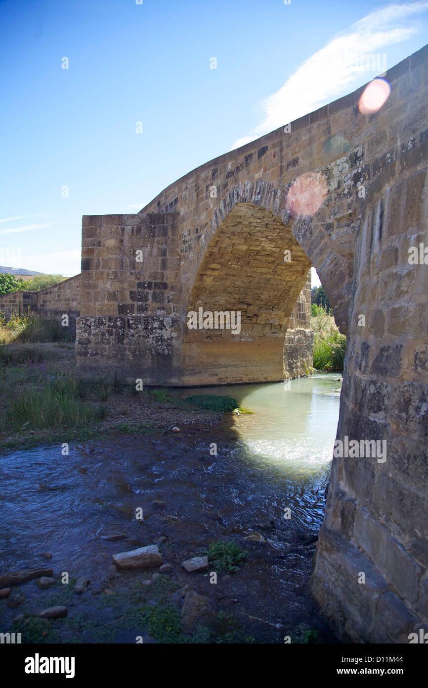 a stone bridge and sunflare, a shady spot along the French Route of the Camino de Santiago de Compostela - Stock Image