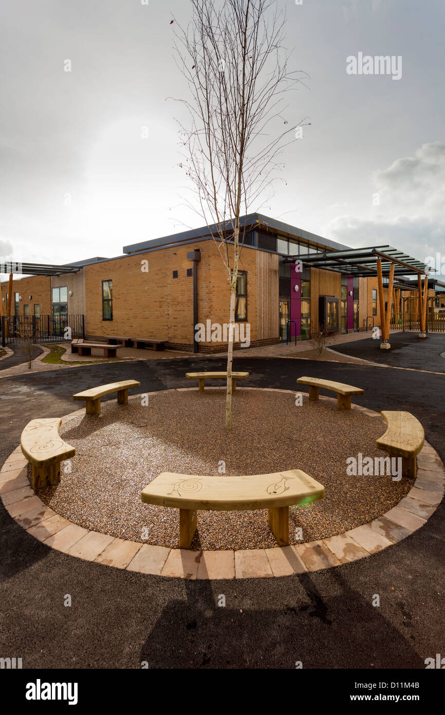 unoccupied bench seats in school playground - Stock Image