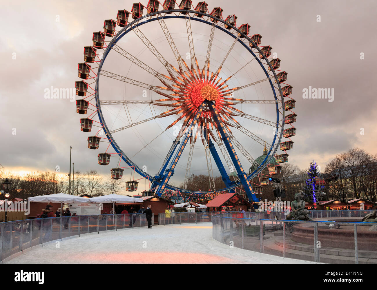 Ice skating rink and big wheel at a traditional Christmas market in the evening at Alexanderplatz, Berlin, Germany Stock Photo