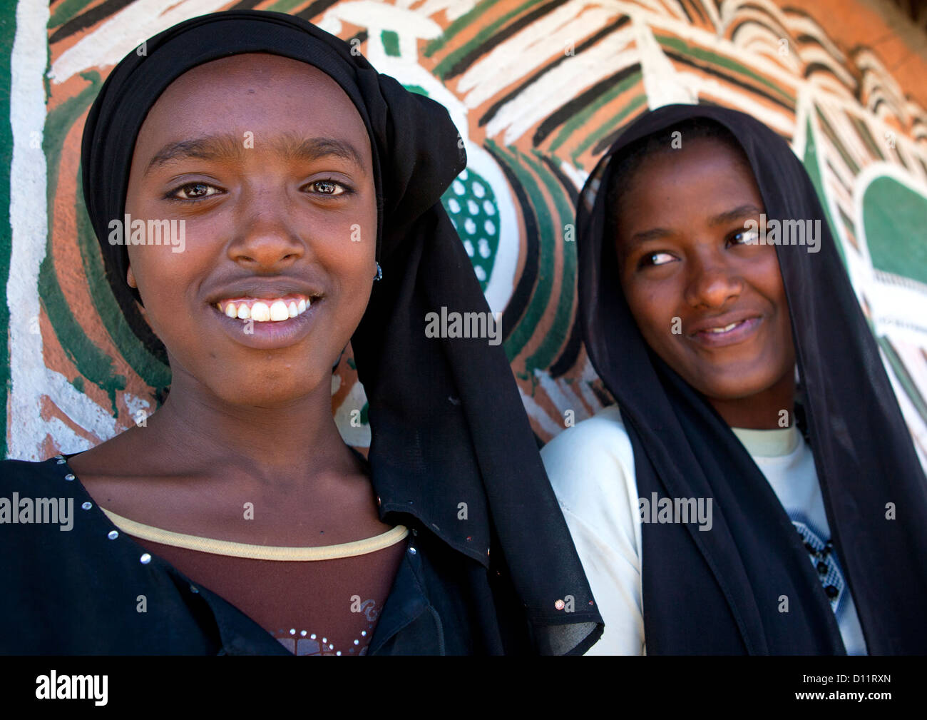 Portrait Of Muslim Ethiopian Girls With Toothy Smiles And Black Veils Outside A Painted Tukul, Alaba, Ethiopia - Stock Image
