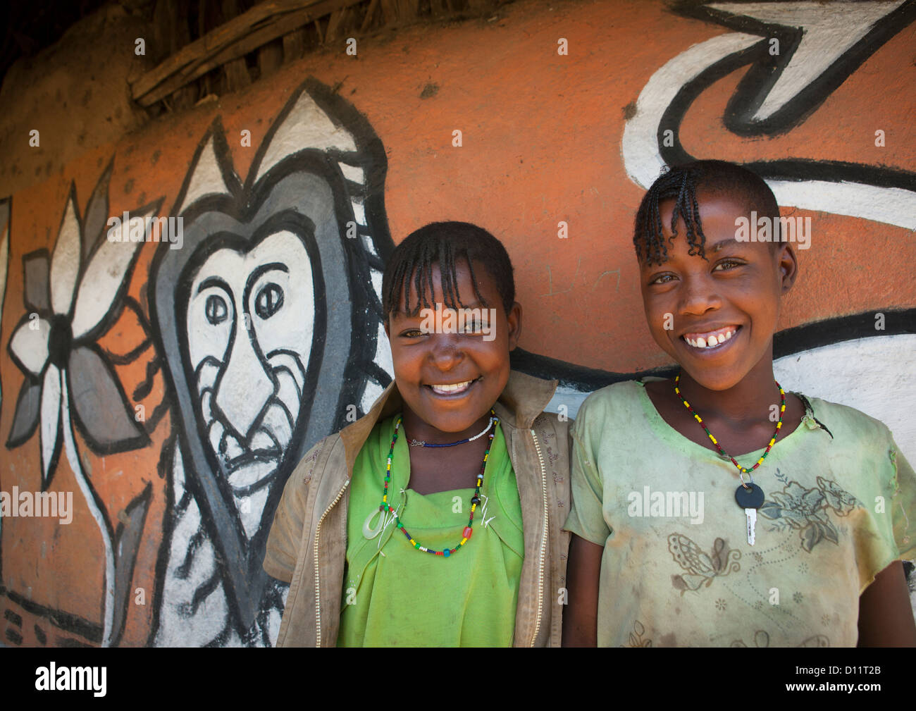 Portrait Of Smiling Girls With Toothy Smiles In Front Of Their Decorated House, Alaba, Ethiopia - Stock Image