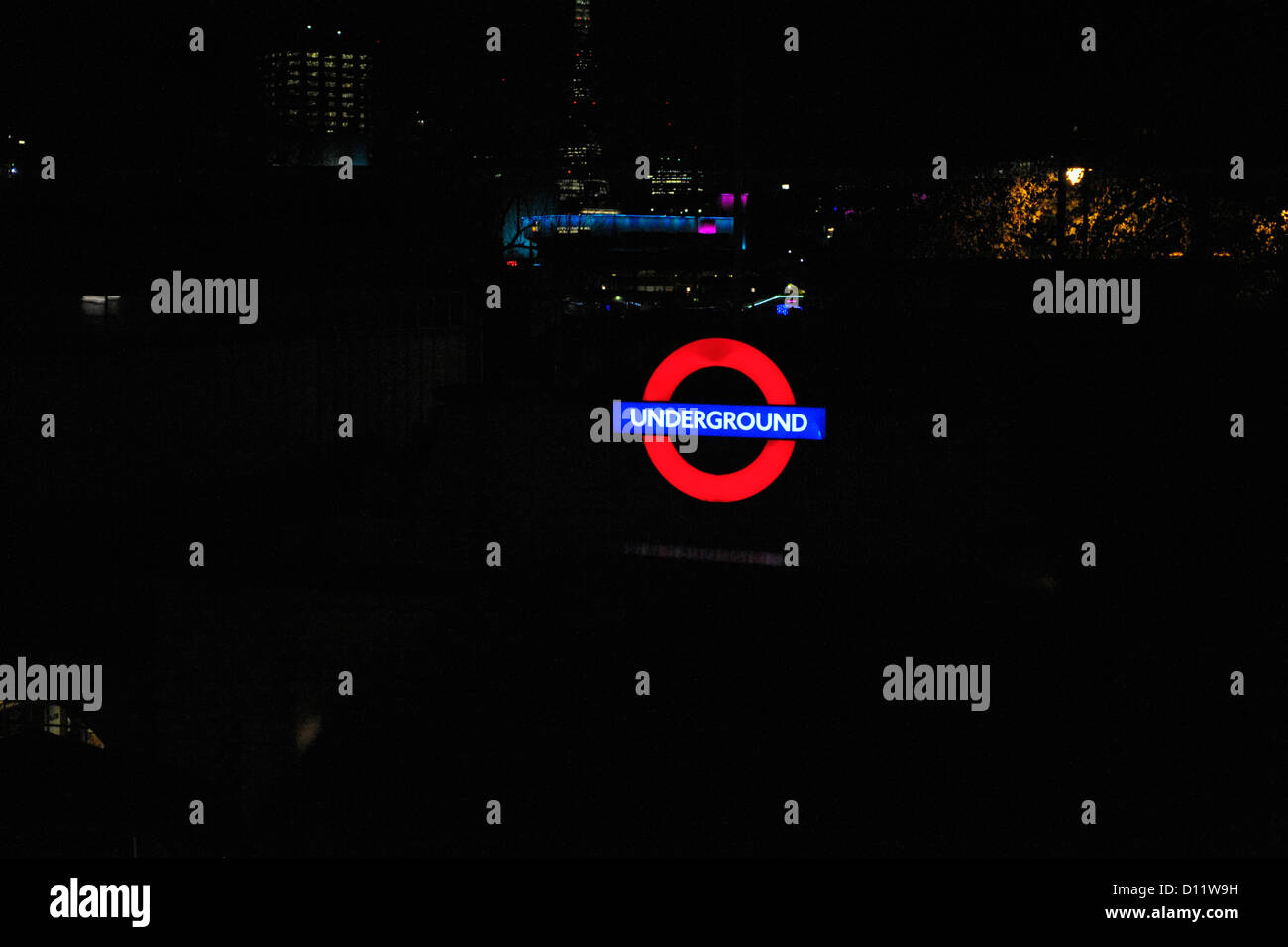 Illuminated London underground tube sign, with dark background for copy space. Some glimmers of the city at night - Stock Image