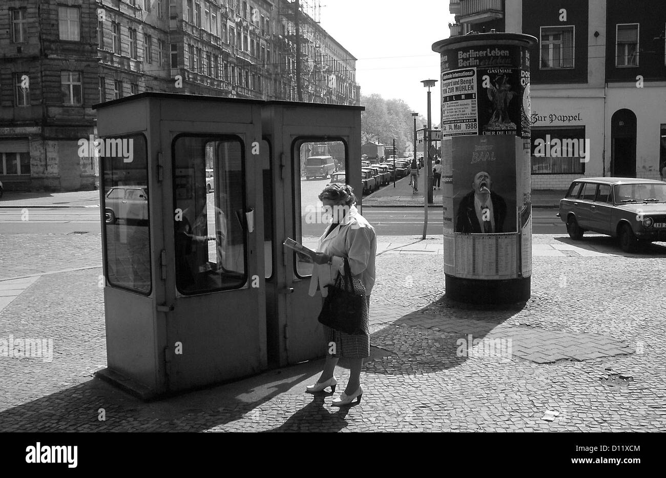 Berlin, GDR, a woman stands in front of phone booths in Prenzlauer Berg - Stock Image