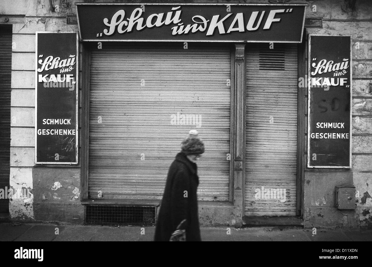 Halle, East Germany, a woman walks past a closed business Stock Photo