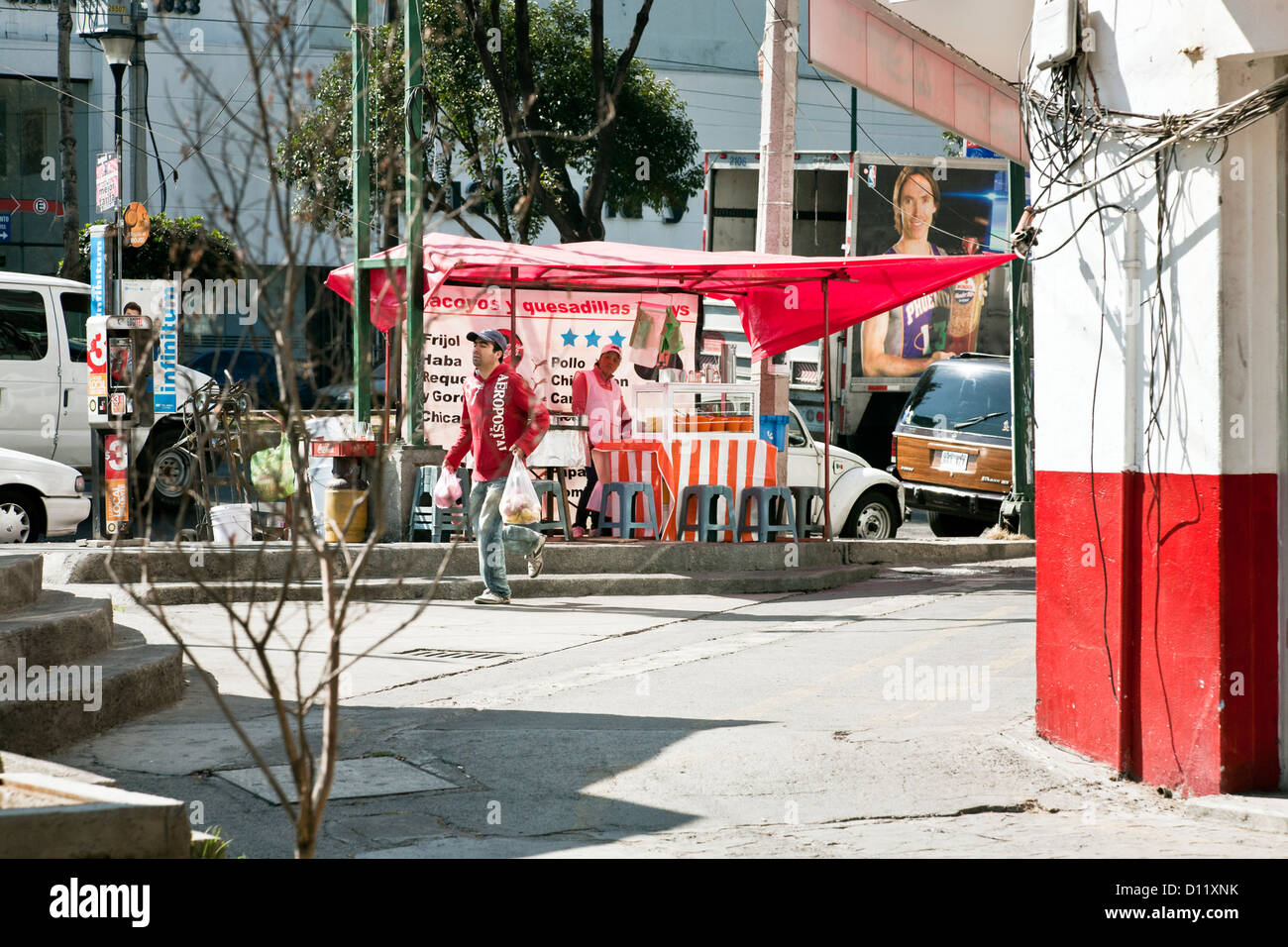 street corner scene with colorful taco & quesadilla stand on beautiful sunny day in outlying commercial district - Stock Image