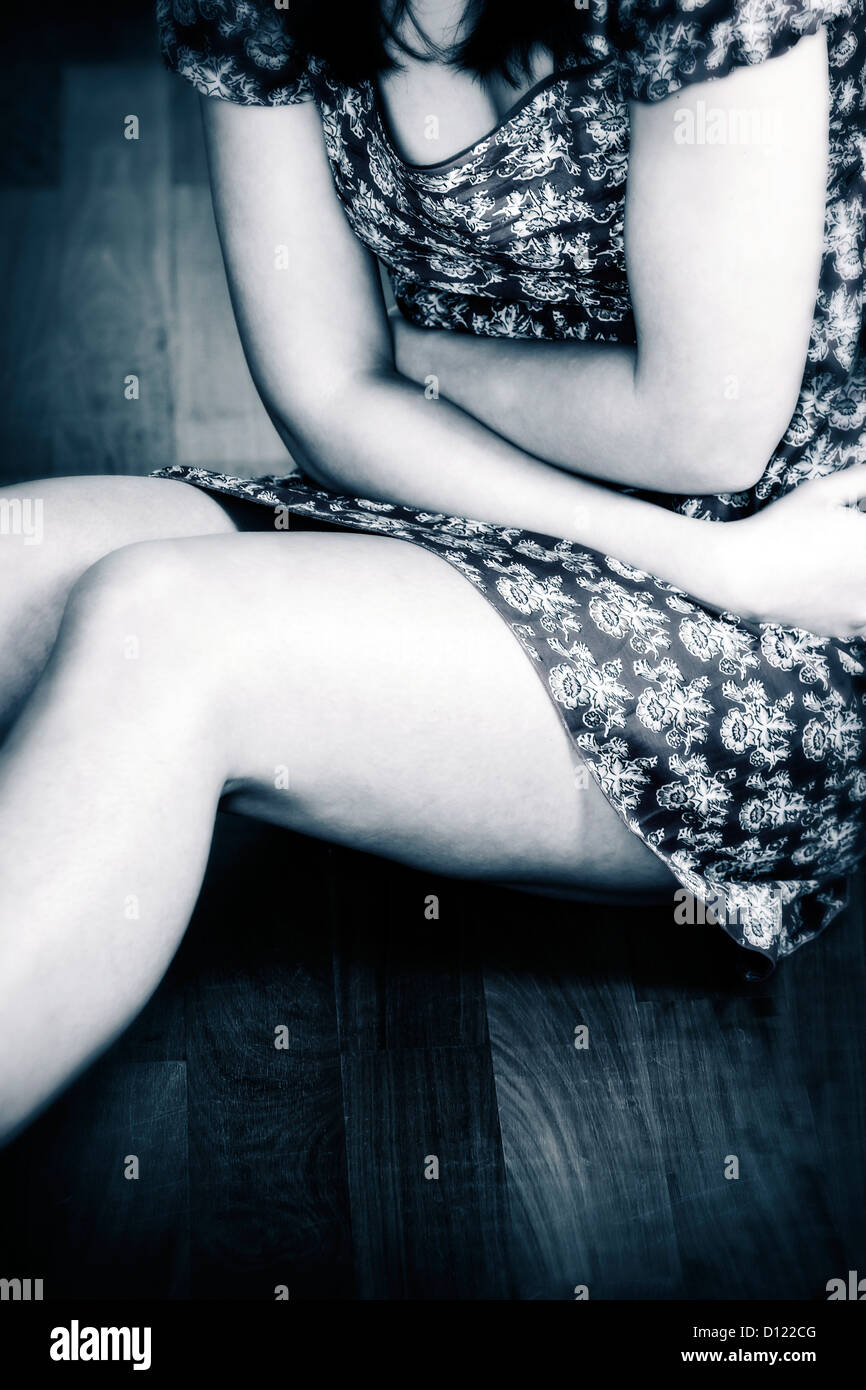detail view of a girl sitting on a wooden floor, hugging herself - Stock Image
