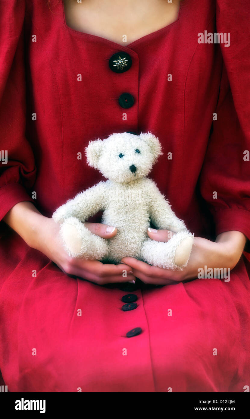 a woman in a red dress with a teddy bear on her lap - Stock Image