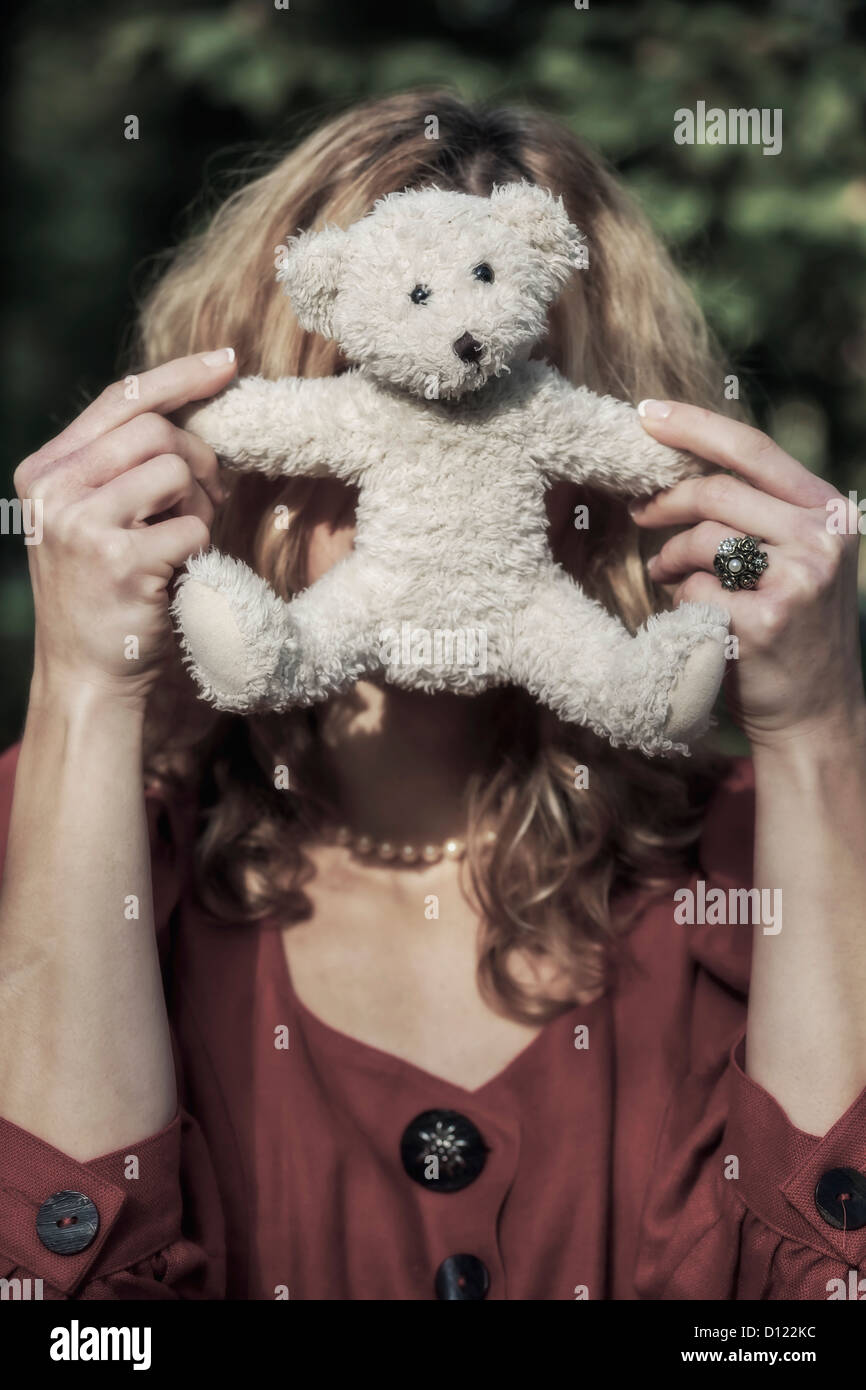 a woman is hiding behind a white teddy bear - Stock Image