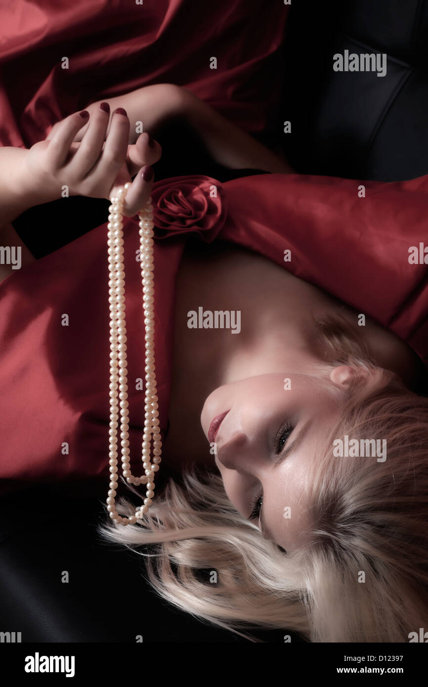 a blond woman is lying on a black sofa, holding a pearl necklace - Stock Image