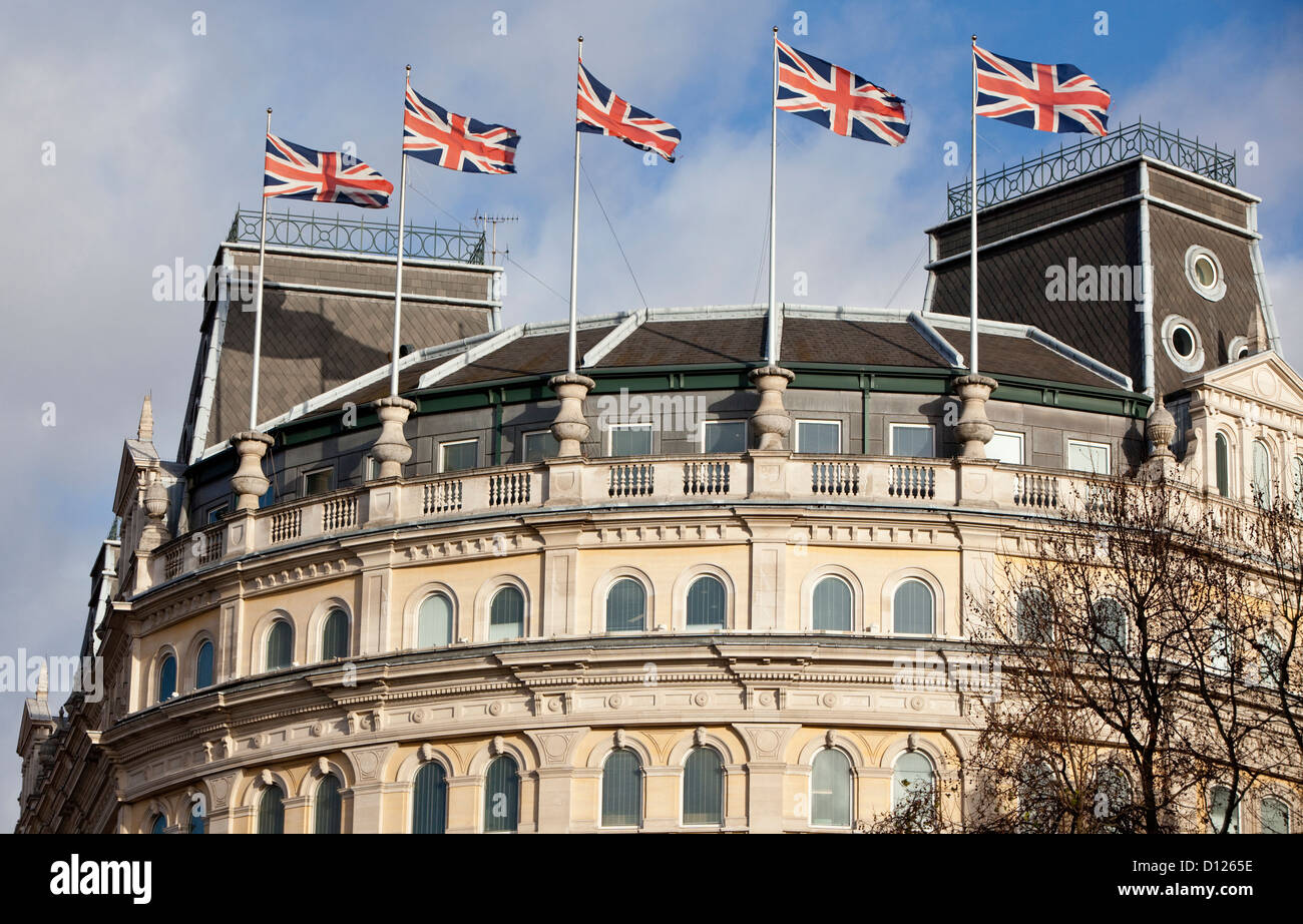 Union Flags fluttering on top of the Grand Buildings Building, London, England, UK - Stock Image