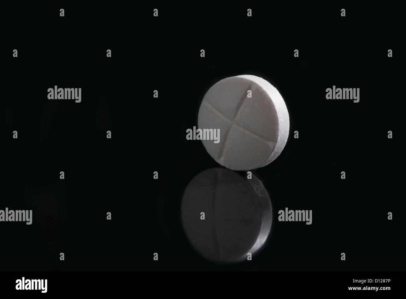 Close Up Of A Single White Pill With Cross Marks Backlit On A Black Reflective Surface; Calgary Alberta Canada Stock Photo