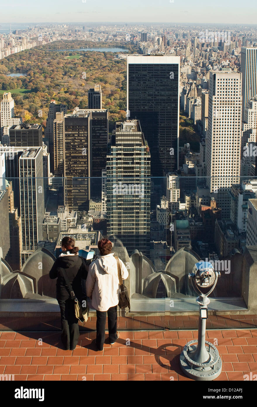 "Two tourists standing on ""top of the Rock"" looking north at Central park, in autumn, fall. Stock Photo"