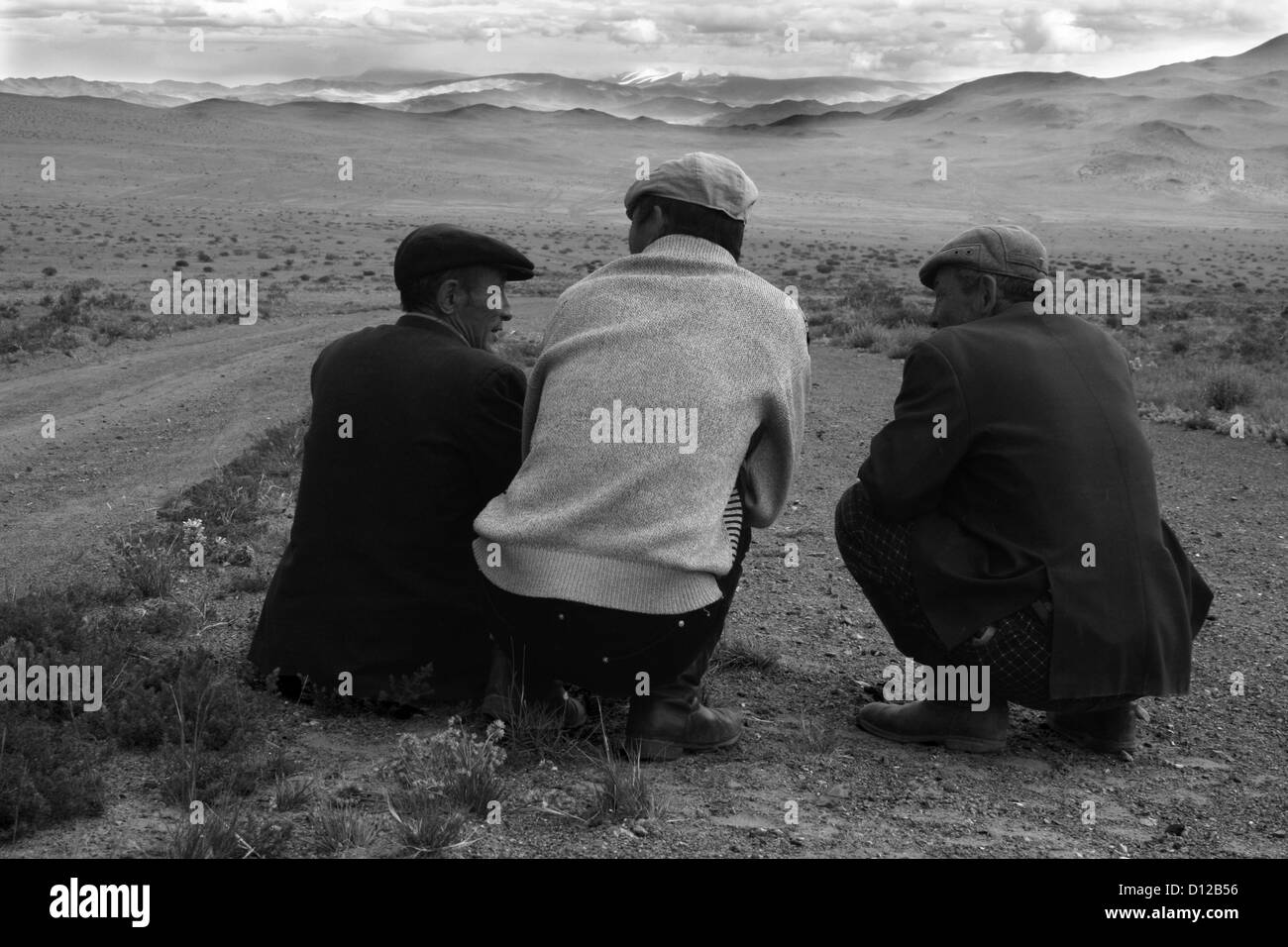 Old men waiting for the engine of the van to cool down, on the road from Ulaankhus to Olgii - Stock Image