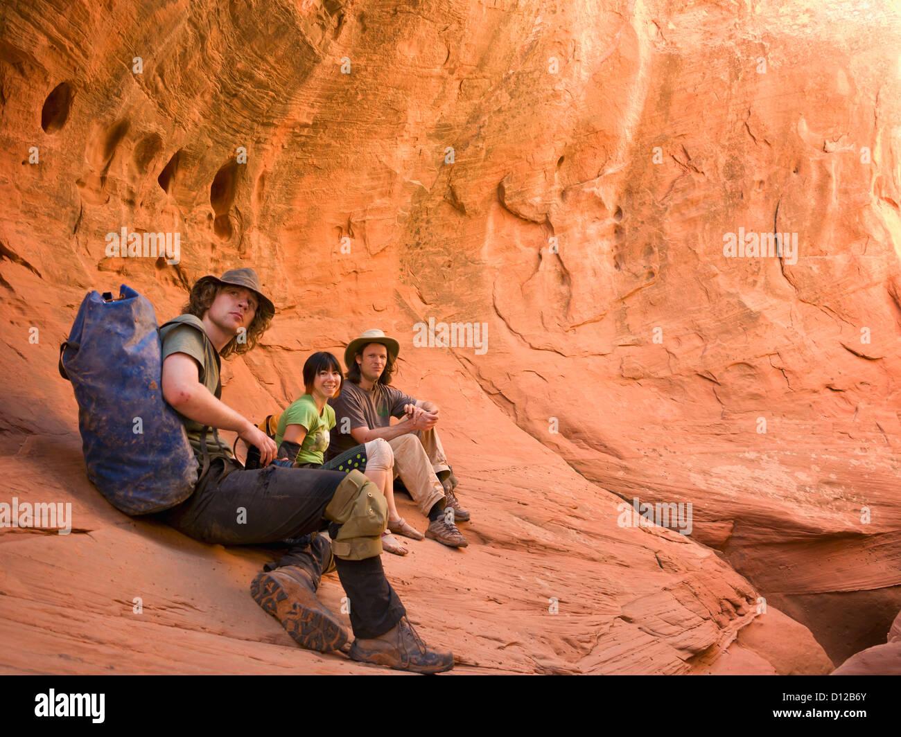 A Group Of Adventure Athletes Exploring Utah Slot Canyons; Hanksville Utah United States Of America - Stock Image