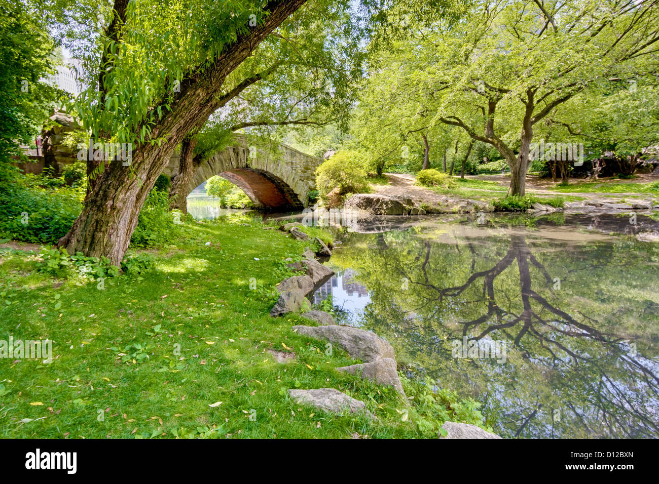 A stone bridge in Central Park, NY. There is a large tree and reflection in the pond that runs under the bridge. - Stock Image